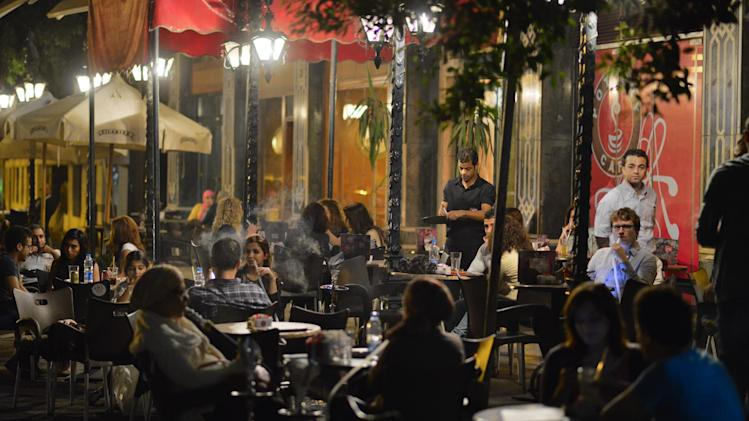Egyptians relax outside a cafe in Cairo, Egypt, Wednesday, Oct. 31, 2012. Egypt's capital prides itself on being city that never sleeps, with crowds filling cafes and shops open into the small hours. So the government is facing a backlash from businesses and the public as it vows to impose new nationwide rules closing stores and restaurants early. Officials say the crisis-ridden nation has to conserve electricity, but they also seem intent on taming a population they see as too unruly.  (AP Photo)
