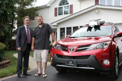 Bill Fay, Toyota Motor Sales, U.S.A., Inc. group vice president and general manager of the Toyota Division, surprises Michael Dee -- Toyota's 50 millionth customer -- with a brand new RAV4 and paid off car loans