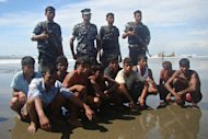 Rohingya refugees, who survived after their overloaded boat heading to Malaysia sank, are seen under the custody of Bangladeshi border guards (background, standing) at a beach in Teknaf on November 7, 2012. The UN's refugee agency on Friday raised the alarm over the rising number of boat people perishing in the Indian Ocean, including Rohingya Muslims fleeing communal strife in Myanmar