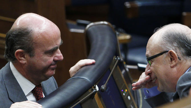 Spain's Minister of Economy and Competitiveness Luis de Guindos, left, and The Minister for the Treasury and Public Administration Services Cristobal Montoro, right, speak during a control session at the Spanish Parliament, in Madrid, Spain, Wednesday, July 18, 2012. He was defending a euro 65 billion austerity package that includes tax hikes and spending cuts announced last week after winning approval from euro zone partners for a huge bailout of Spain's troubled banks. (AP Photo/Andres Kudacki)