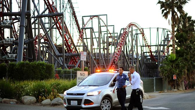 Members of the Six Flags Magic Mountain amusement park security staff monitor the situation at the exit of the park after riders were injured on the Ninja coaster, not shown, Monday, July 7, 2014, in Valencia, Calif. The roller coaster hit a tree branch dislodging the front car, leaving four people slightly injured and keeping nearly two dozen summer fun-seekers hanging 20 to 30 feet in the air for hours as day turned to night. Two of the four people hurt on the Ninja coaster were taken to the hospital as a precaution, but all the injuries were minor, fire and park officials said. (AP Photo/Los Angeles Daily News, Andy Holzman)