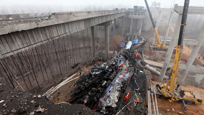 In this Feb. 1, 2013 photo provided by China's Xinhua News Agency, rescuers work at the accident site where an 80-meter (260 foot) section of an expressway bridge collapsed in Mianchi County, Sanmenxia, central China's Henan Province.   An elevated portion of highway in central China collapsed on Friday after a truck loaded with fireworks for Lunar New Year celebrations exploded, killing at least nine people and sending vehicles plummeting 30 meters (about 100 feet) to the ground. (AP Photo/Xinhua, Zhang Xiaoli) NO SALES