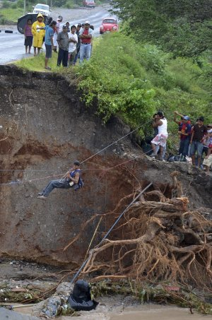 Residents use a makeshift zip line to cross after a…