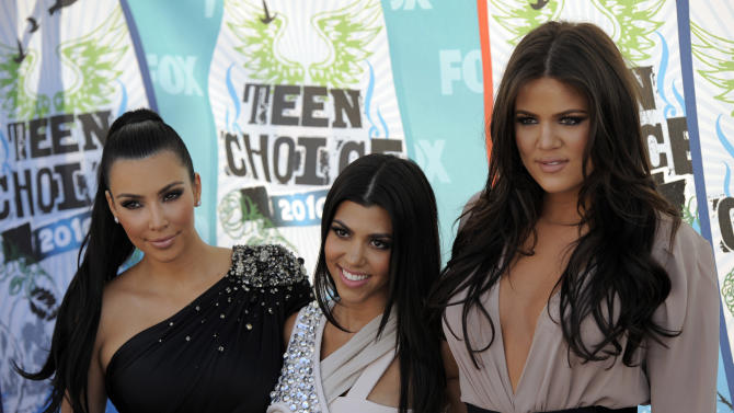 FILE - In this Aug. 8, 2010 file photo, from left, Kim Kardashian, Kourtney Kardashian and Khloe Kardashian arrive at the Teen Choice Awards in Universal City, Calif.  E! Entertainment network  announced that they are expanding reality programming on their network in additoin to having renewed the Kardashians series for 3 years. (AP Photo/Chris Pizzello, File)