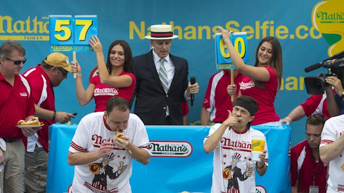 Joey Chestnut (L) and Matt Stonie (R) consume hot dogs during the annual Fourth of July 2015 Nathan's Famous Hot Dog Eating Contest in Brooklyn, New York
