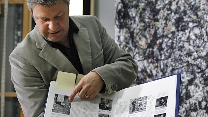 Nicholas Dorman, chief conservator for the Seattle Art Museum, explains how he referred to old photos to help get information to help in his on-going restoration work of Jackson Pollock's painting Sea Change during a news conference Tuesday, Nov. 27, 2012, at the museum in Seattle. The celebrated piece, part of SAM's permanent collection, was painted in 1947 and altered in 1970 with a coat of varnish. Dorman is several months into the restoration work, which is complicated by the uneven surface and multiple layers of media, including several types of paint and imbedded gravel. The restoration is sponsored by Bank of America's Art Conservation Project, which enabled SAM staff and consulting experts to undertake a study of the original materials and evaluate the impact of materials used in conservation treatments. (AP Photo/Elaine Thompson)