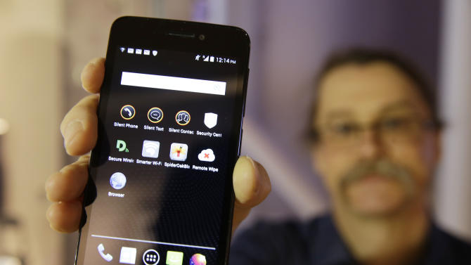 FILE - In this July 30, 2014, file photo, Silicon Valley pioneer and Silent Circle co-founder Jon Callas holds up Blackphone with encryption apps displayed on it at the Computer History Museum in Mountain View, Calif. The Paris terrorist attacks have renewed the debate between law-enforcement officials and privacy advocates over whether there should be limits to encryption technology. (AP Photo/Eric Risberg, File)