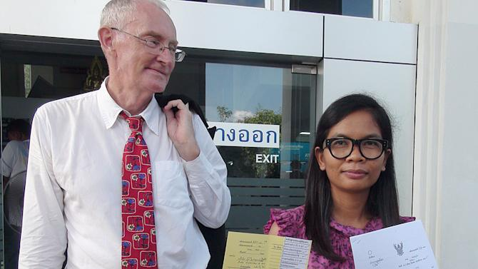 Alan Morison of Australia, editor of The English-language news website Phuketwan, left, and his Thai colleague, Chutima Sidasathien, right, walk out during a break at Phuket provincial courtroom in Phuket, southern Thailand Thursday, April 17, 2014. Thai authorities on Thursday charged two journalists with defaming Thailand's navy in an online news report about the trafficking of refugees from Myanmar, amid concerns about press freedom in the country. The court's appointment documents are held by Chutima. (AP Photo/Krissada Muanhawong)