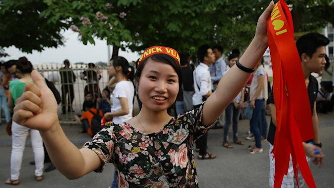 In this Thursday, May 23, 2013 photo, a Vietnamese girl sells headbands printed the name of Nick Vujicic, a Serbian Australian evangelist outside My Dinh national stadium in Hanoi, Vietnam. Vujicic was born with tetra-amelia syndrome, a rare disorder characterized by the absence of all four limbs. Amid childhood bullying, he once tried to drown himself. (AP Photo/Na Son Nguyen)