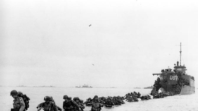 FILE - U.S. reinforcements wade through the surf from a landing craft in the days following D-Day and the Allied invasion of Nazi-occupied France at Normandy in June 1944 during World War II.  (AP Photo/Bert Brandt, File)