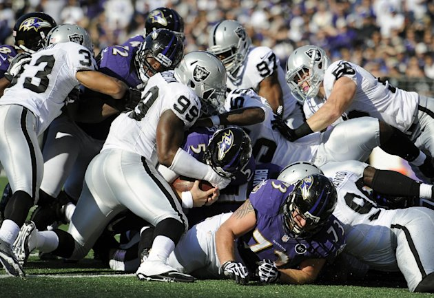 Baltimore Ravens quarterback Joe Flacco (5) falls into the end zone for a touchdown in the first half of an NFL football game against the Oakland Raiders in Baltimore, Sunday, Nov. 11, 2012. (AP Photo
