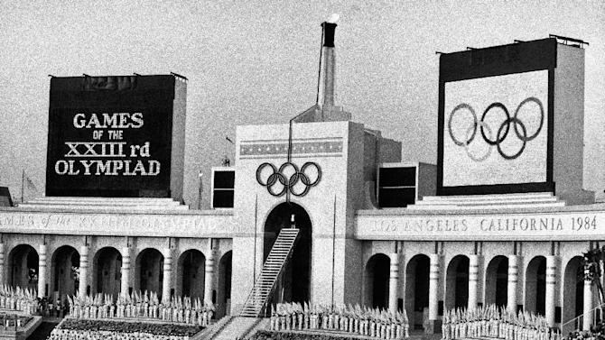 FILE - In this July 28, 1984, file photo, the Olympic flame is flanked by a scoreboard signifying the formal opening of the XXIII Olympiad after it was lit by Rafer Johnson during the opening ceremonies in the Los Angeles Memorial Coliseum. Embarrassing as it was, the U.S. Olympic Committee won't necessarily be remembered for its ungainly dumping of Boston as a bid city for the 2024 Olympics. The USOC has seven weeks to get another city on board _ and it could be Los Angeles. (AP Photo/Eric Risberg, File)