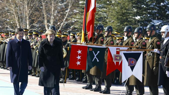 Turkish Prime Minister Davutoglu and German Chancellor Merkel review the Guard of Honour during a welcoming ceremony in Ankara