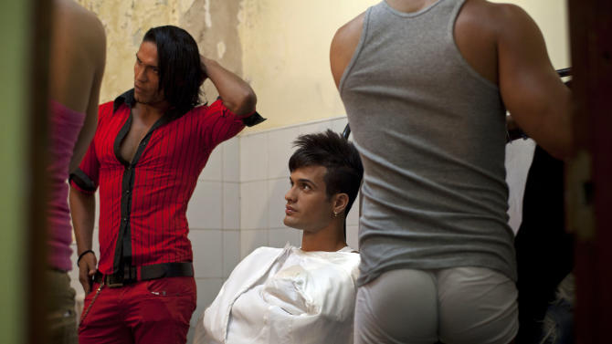 In this May 11, 2013 photo, dancers gather backstage to prepare for their presentation against homophobia at the Karl Marx theater in Havana, Cuba. A week of drag shows, colorful marches and social and cultural events in Havana culminates Friday with celebrations of the International Day Against Homophobia. Gays were persecuted for decades after the 1959 Cuban Revolution, sometimes sent to grueling rural work camps along with others considered socially suspect by the Communist government. But there has been a gradual shift away from macho attitudes, and Fidel Castro himself has publicly regretted the mistreatment of people seen as different. (AP Photo/Ramon Espinosa)