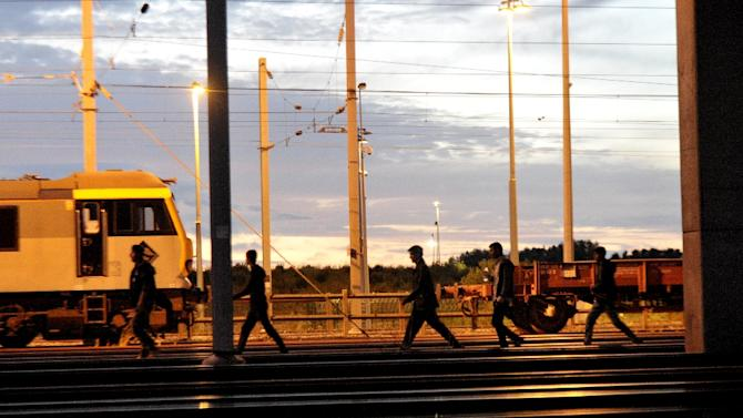 Migrants walk along the railway tracks of the Eurotunnel terminal at the Calais-Frethun station in France on August 10, 2015