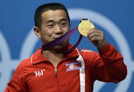 North Korea&#39;s Om Yun Chol celebrates with his gold medal on the podium for the weightlifting men&#39;s 56kg at the Excel Center in London during the 2012 London Olympic Games