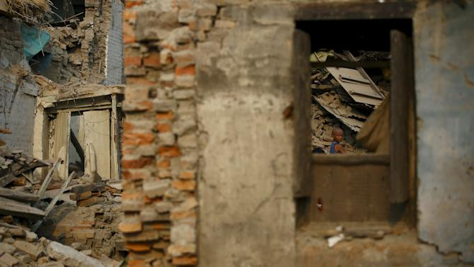 A boy is seen through the window of a collapsed house after the April 25 earthquake at Bhaktapur