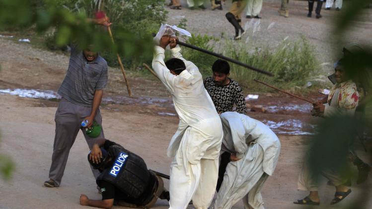 Anti-government protesters beat a riot policeman after clashes during the Revolution March in Islamabad
