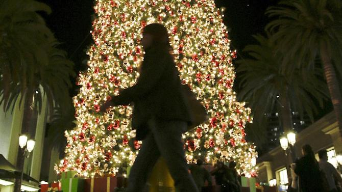 In this Thursday, Dec. 20, 2012, photo, a holiday shopper walks past a large Christmas tree at Fashion Island shopping center in Newport Beach, Calif. Holiday shopping, strong auto sales and a recovering housing market helped boost the U.S. economy from the middle of November through early January, according to a Federal Reserve survey released Wednesday.  (AP Photo/Chris Carlson)