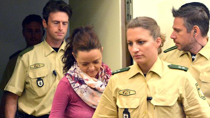 """FILE - In this Aug, 6, 2014 file picture defendant Beate Zschaepe , center, enters the court room at the Higher Regional Court in Munich, Germany. Beate Zschaepe is accused of being a founding member of the far right National Socialist Underground (NSU) terror cell and faces charges of complicity in the murder of nine Turkish and Greek immigrants and a policewoman between 2000 and 2007 An official inquiry has concluded that police and security services in Germany bungled the hunt for three neo-Nazis who years later turned out to be the main suspects in a far-right murder spree. Lawmakers in the eastern state of Thuringia say efforts to find the fugitive trio after their disappearance in 1998 were a """"complete disaster."""" A 1,895-page report published Thursday Aug. 21, 2014 lists a string of errors by investigators who failed to follow up leads that could have led to the arrest of the group calling itself National Socialist Underground. (AP Photo/dpa, Peter Kneffel,file)"""