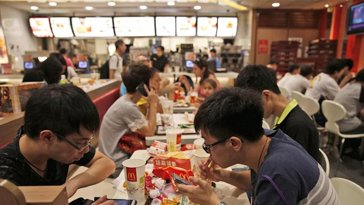 Customers eat at a McDonald's restaurant in Hong Kong Friday, July 25, 2014. McDonald's restaurants in Hong Kong have taken chicken nuggets and chicken filet burgers off the menu after a U.S.-owned supplier in mainland China was accused of selling expired meat. (AP Photo/Kin Cheung)
