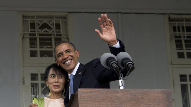 U.S. President Barack Obama waves to the media as he stands with Myanmar opposition leader Aung San Suu Kyi at her residence in Yangon, Myanmar, Monday, Nov. 19, 2012. Obama touched down Monday morning, becoming the first U.S. president to visit the Asian nation also known as Burma. (AP Photo/Carolyn Kaster)