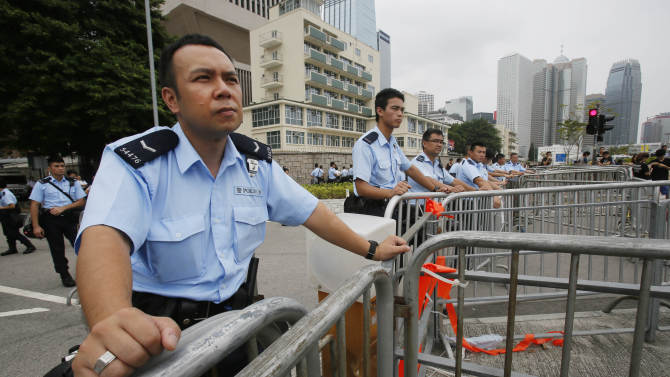 Police guard barriers around the student occupied streets around the government complex in Hong Kong, Thursday, Oct. 2, 2014. Raising the stakes in their standoff with the authorities, Hong Kong's pro-democracy protesters threatened to occupy key government buildings unless the territory's top official resigns by the end of the day Thursday. (AP Photo/Wally Santana)
