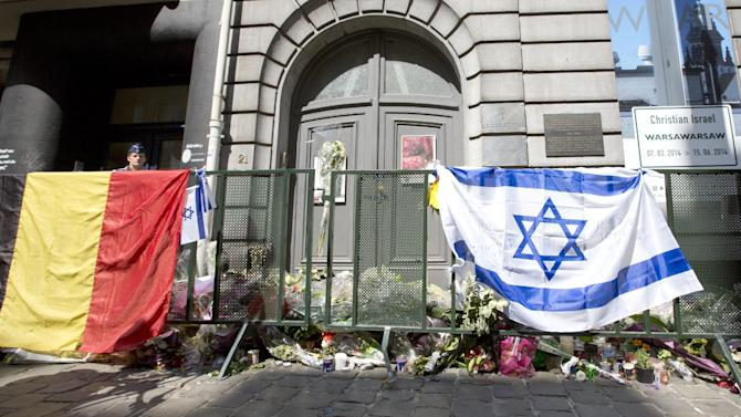 The Belgian and Israeli flag hang on a rail in front of candle and flower tributes a for the victims of a shooting at the Jewish Museum in Brussels, on Monday, June 2, 2014. Police have arrested a suspect after three people were killed and one seriously injured in a spree of gunfire at the Jewish Museum in Brussels on Saturday, May 24, 2014. (AP Photo/Virginia Mayo)
