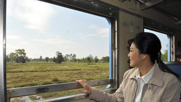 Thailand's Prime Minister Yingluck Shinawatra looks out from a train window during her trip from Surin province to Sisaket province