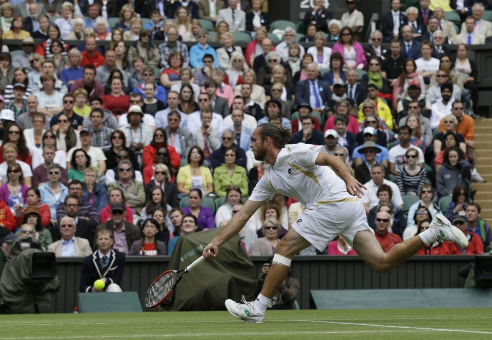 Xavier Malisse of Belgium plays a return to Roger Federer of Switzerland during a  fourth round singles match at the All England Lawn Tennis Championships at Wimbledon, England, Monday, July 2, 2012. (AP Photo/Anja Niedringhaus)