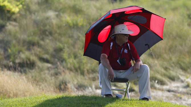 A marshall takes cover under an umbrella on the 13th green during the first round of the U.S. Women's Open golf tournament, Thursday, July 5, 2012, in Kohler, Wis. (AP Photo/Jeffrey Phelps)
