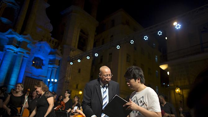 Cuban pianist and Grammy winner Chucho Valdes talks to pianist Lang Lang from China before a concert at the Cathedral Square in Havana