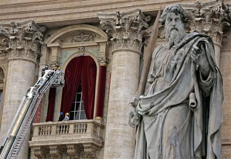 Workers put up a red curtain on the central balcony, called the Loggia of the Blessings of Saint Peter's Basilica at the Vatican
