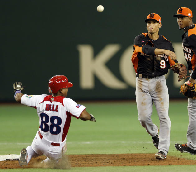 Netherlands' shortstop Andrelton Simmons (9) throws first for a double play as Cuba's rightfielder Alexei Bell slide into second in the third inning of their World Baseball Classic second round game i