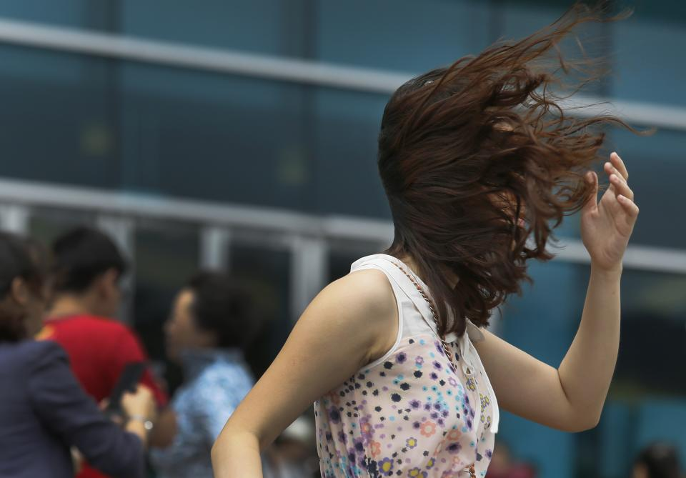 A tourist from mainland China braves strong wind near the waterfront in Hong Kong Wednesday, Aug. 14, 2013. Typhoon Utor lashed Hong Kong with wind and rain, closing down the bustling Asian financial center Wednesday before sweeping toward mainland China.(AP Photo/Vincent Yu)