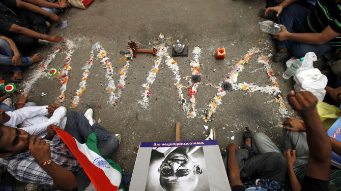 """Supporters of anti-corruption activist Anna Hazare place a portrait of Mahatma Gandhi, bottom, near a marking on the road that reads """"Anna"""" outside the Tihar prison where Hazare was holding his hunger strike in New Delhi, India, Wednesday, Aug. 17, 2011. Prime Minister Manmohan Singh lashed out at India's most prominent anti-corruption crusader Wednesday, accusing the fasting activist of trying to circumvent democracy by demanding Parliament pass a reform bill he supports. (AP Photo/Gurinder Osan)"""