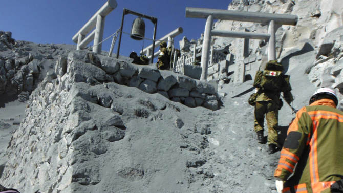 In this Sunday, Sept. 28, 2014 photo released by Nagoya City Fire Dept., Japan Ground Self-Defense Force personnel and Nagoya city firefighters climb the ash-covered slope to the mountaintop shrine for their rescue operation on the Mount Ontake in central Japan. Increased seismic activity raised concern Tuesday about the possibility of another eruption at a Japanese volcano where dozens of people were killed by Saturday's initial eruption, forcing rescuers to suspend plans to try to recover at least two dozen bodies still near the summit. (AP Photo/Nagoya City Fire Dept.) EDITORIAL USE ONLY