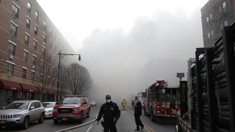 Smoke fills East 116th street near an apparent building explosion fire and collapse in the Harlem section of New York City