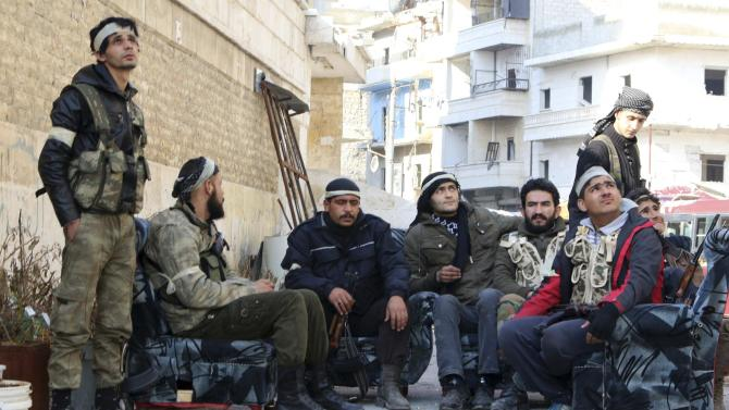 Group 16 fighters, part of the Free Syrian Army, rest with their weapons during what activists said were violent clashes with forces loyal to Syria's President Bashar al-Assad in Ashrafieh, Aleppo