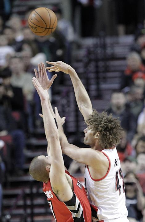 Portland Trail Blazers center Robin Lopez, right, shoots over Toronto Raptors center Jonas Valanciunas during the first half of an NBA basketball game in Portland, Ore., Saturday, Feb. 1, 2014