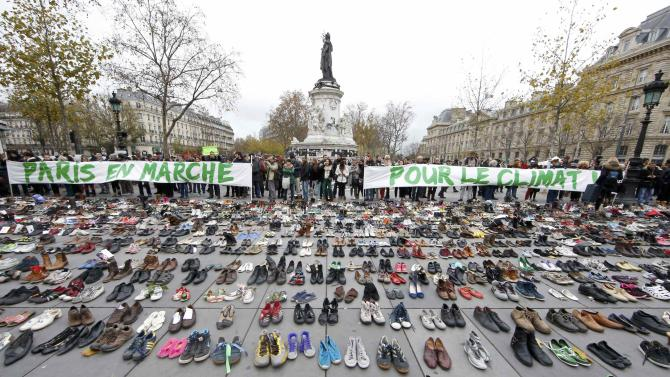 """Banners which read """"Paris marches for climate change"""" are displayed in front of pairs of shoes symbolically placed on the Place de la Republique ahead of the World Climate Change Conference 2015 in Paris"""