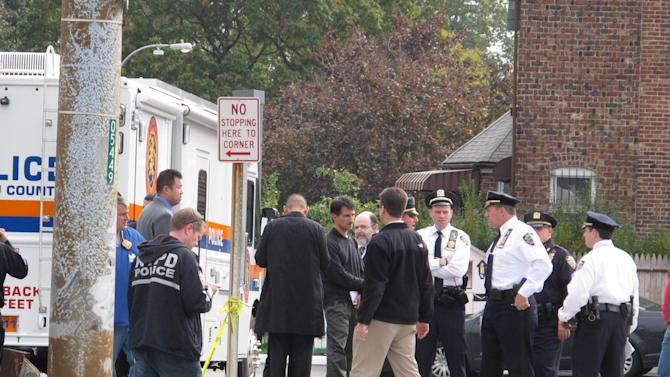 Police officers investigate at the scene of a shooting in Bellerose Terrace, N.Y., Tuesday, Oct. 24, 2012. A police officer on New York's Long Island and another person were killed after shooting erupted Tuesday morning during what a witness described as a routine traffic stop at the New York City limits on Long Island. (AP Photo/Frank Eltman)
