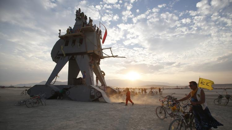 "Participants interact with the Alien Siege Machine during the Burning Man 2014 ""Caravansary"" arts and music festival in the Black Rock Desert of Nevada"