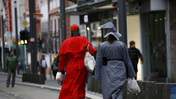 Carnival revellers stroll along a near empty street during Rosenmontag in Mainz