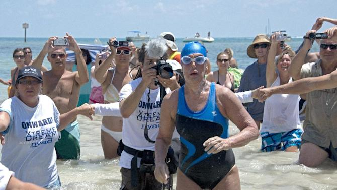 In this photo provided by the Florida Keys News Bureau Diana Nyad emerges from the Atlantic Ocean after completing a 111-mile swim from Cuba to Key West, Fla. Nyad, 64, is the first swimmer to cross the Florida Straits without the security of a shark cage. The swim took Nyad 52 hours and 54 minutes, according to a support team member. (AP Photo/Florida Keys Bureau, Andy Newman)