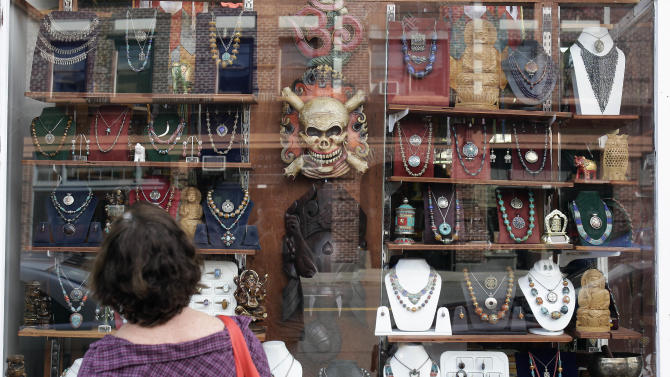 This April 30, 2013, image shows a window-shopper looking at merchandise on display in a store on Hawthorne Boulevard in Portland, Ore. Hawthorne is known for its funky stores and vintage clothing shops, and is a great place for tourists to visit to soak up the people-watching scene. (AP Photo/Don Ryan)