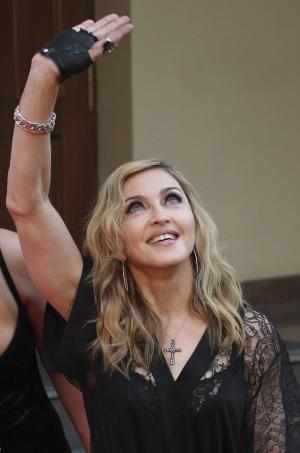 "U.S. singer Madonna greets her fans at the opening of the new fitness club in Moscow, Russia, Monday, Aug. 6, 2012. Madonna has voiced hope that three feminist Russian rockers on trial for performing a ""punk prayer"" against Vladimir Putin are released soon. The pop star told the AP during her concert tour of Russia that she supports freedom of speech and hopes the judge will show leniency. (AP Photo/Mikhail Metzel)"