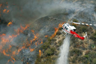 A Los Angeles County Firefighter helicopter drops water on a wildfire burning through 3,600 acres of the Angeles National Forest on Tuesday Sept. 4, 2012 near Glendora, Calif. It could be a week before firefighters can contain the blaze because of high temperatures and rugged terrain in thick brush that hasn't burned in a couple of decades. (AP Photo/Nick Ut)