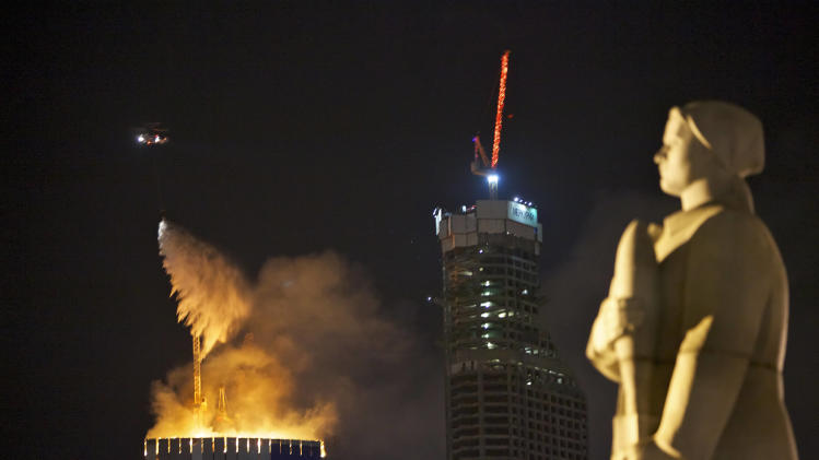 A firefighting helicopter drops water to extinguish fire atop an under-construction skyscraper, planned to be Europe's tallest building, in Moscow, Russia, Monday, April 2, 2012, with the statue of a woman-defender of Moscow in WWII, foreground right. Orange flames were leaping about 250 meters (880 feet) Monday, visible in the night sky to much of the city. No injuries have been reported at the fire in the eastern tower of the Federation Tower complex, part of a massive development along the Moscow River about 2.5 kilometers (1.5 miles) west of the Kremlin. The tower, when completed, is to be 360 meters (1150 feet) tall. (AP Photo/Alexander Zemlianichenko)