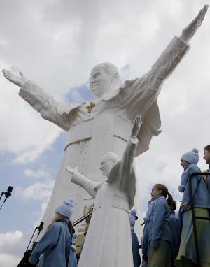 A children's choir takes part in the unveiling ceremony of the statue of the late Pope John Paul II in Czestochowa, Poland, on Saturday, April 13, 2013. Archbishop Waclaw Depo unveiled the 13.8-meter (45.3-foot) white fiberglass figure that was funded by a businessman, Leszek Lyson, in gratitude for what he believes was an intervention by the late pontiff in saving his drowning son. At front is a small replica statue. (AP Photo/Czarek Sokolowski)